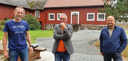 Ole Dybwad, Tommy Reinås og Eivind S Mjøen foran rød bygning i gårdstunet
