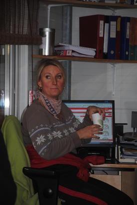 Monica ved datamaskinen som styrer mjølkerobot, mjølking, kraftfôr, brunst og helse.