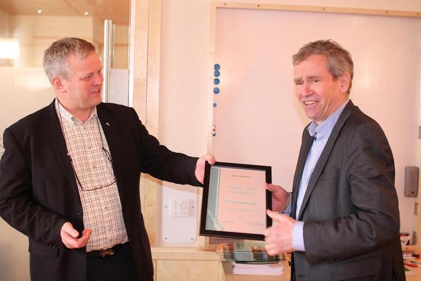 Leder av Norges Bondelag, Nils T. Bjørke, overrekker prisen til en noe overrasket leder av Felleskjøpet Agri, Einar Enger.