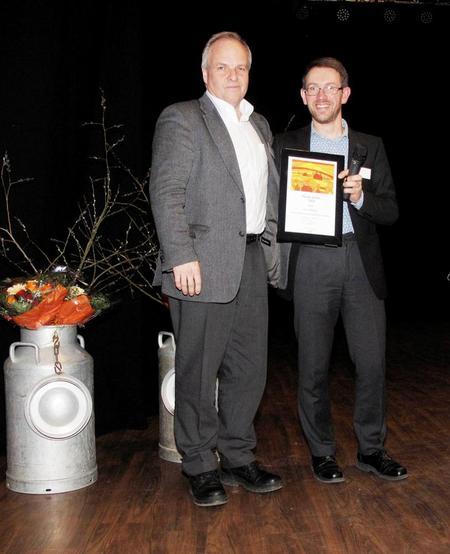 Øyvind Kjølberg får beviset på at han er vinner av årets Stå-på-pris av avtroppende leder i Akershus Bondelag, Odd-Einar Hjortnæs