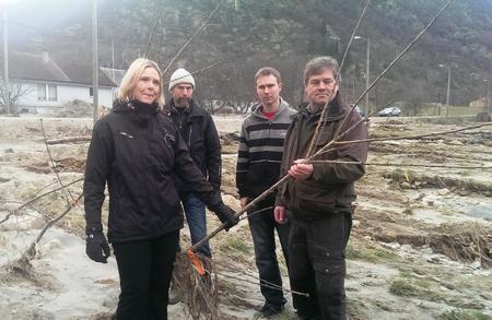 Landbruksminister Sylvi Listhaug og fruktbønder i Lærdal med morelltre som er øydelagt av flaumen.