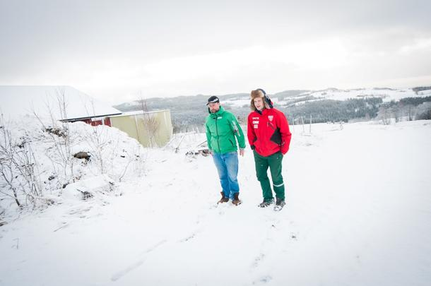 HER KOMMER FJØSET: Kristoffer Moan (t.v.) viser hvor det nye sauefjøset er planlagt. Ved siden av ham står Morten Stefan Berg. Selv om det er snøfall på fjellet nå i juni, er dette bildet tatt i vinter...
