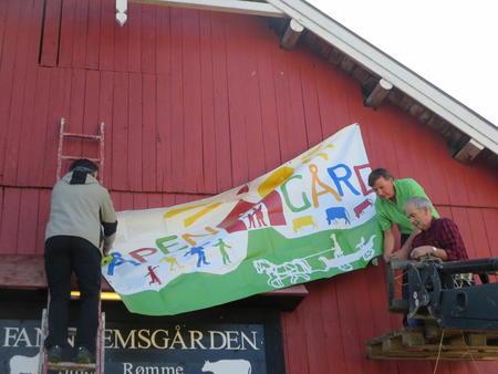 Åpen Gård banneret på plass på fjøsveggen på Fannremsgården