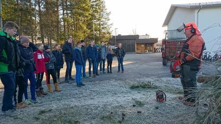 Kåre Ødemark med motorsag og ungdomsskolelever i Skiptvet
