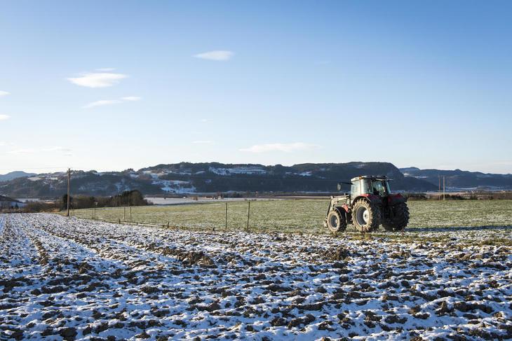 Rød traktor kjører på pløyd delsvis snødekt jorde på Skjetlein