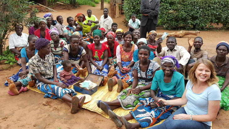 Kvinnene i spare- og lånegruppa i Bwengu viser fram kassen de bruker til å oppbevare penger. Kari Helene Partapuoli, daglig leder i Utviklingsfondet til høyre.  Hun sitter ved siden av leder av sparegruppa, Linly Ngoma