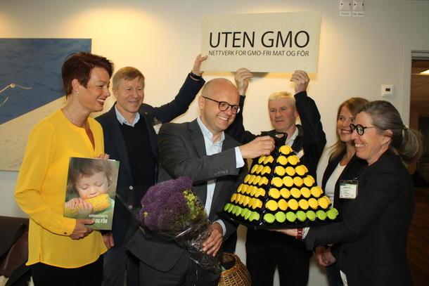 Statsråd Helgesen får godord og kake fra Nettverk for GMO-fri mat og fôr for regjeringas kloke beslutning om å ikke tillate import av GMO-mais og -raps. Foto Helle Berger.