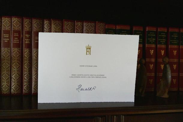 Gratulasjonen frå Kongen står godt synleg i bokhylla.