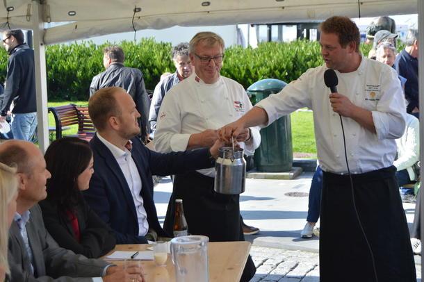 Bondelagskokk Nils Henning Nesje (t.h.) og debattleder Gunnar Nagell Dahl overrakte melkespann til landbruksminister Jon Georg Dale.
