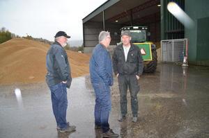 Trond Ellingsbø og Ola Råbøl ute i regnværet og ser på midlertidig lagring av korn på FKs anlegg på Lunner sammen med silosjef Ivar Haglund