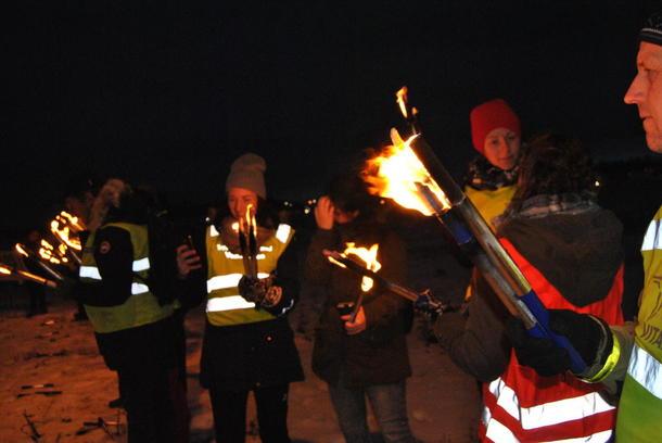 Folk med fakler i mørket demonsterer mot nedbygging av matjord