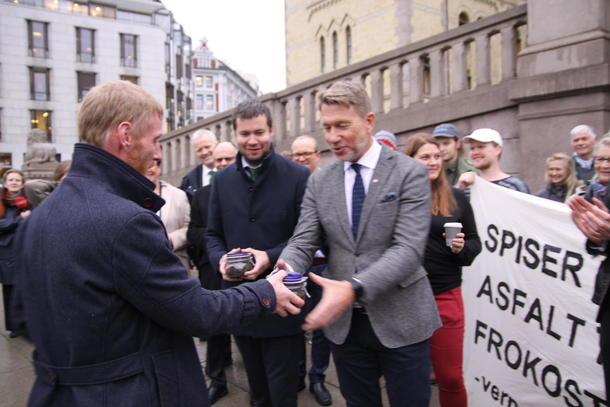 Sven Martin Håland fra Sandnes overleverer trua matjord til Terje Aasland (Ap) Geir Pollestad (Sp).